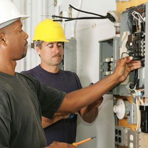 Electricians checkign circuit breakers